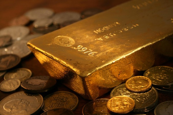 A thick bar of gold sits on a bed of gold coins