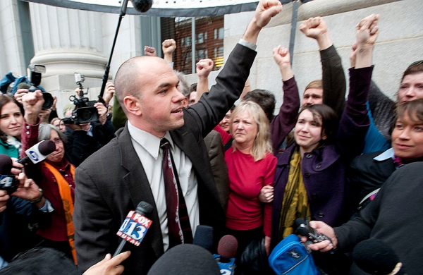 Tim DeChristopher and his supporters, surrounded by media, raise their fists in the air outside a Utah court house.