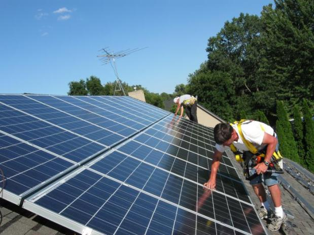 Two men install solar panels on a sunny roof.