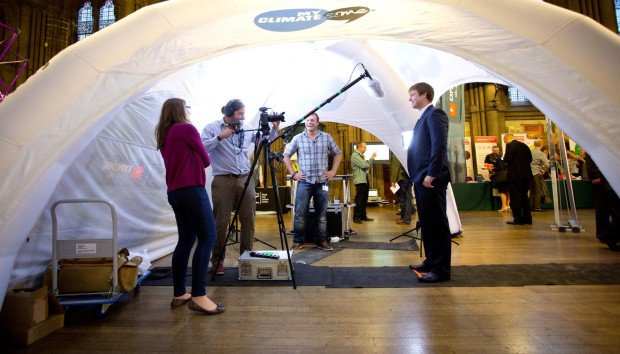 Under a white tent, scientist in suit stands in front of television camera, with onlookers.