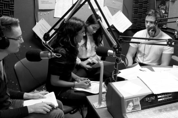 Four people speak in recording studio (photo in black and white)