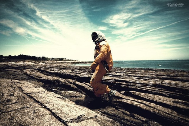 A figure in an orange space suit walks along rocky striations along the coast.